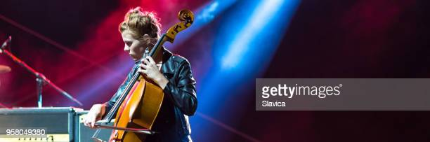 woman playing cello on the stage - filter band stock photos and pictures