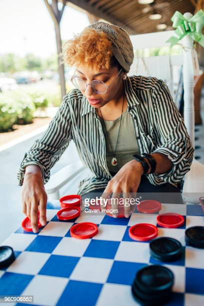 woman playing checkers while sitting at yard - chequers stock photos and pictures