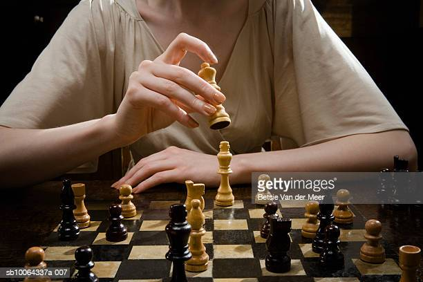 Woman playing chess, holding chess piece, close-up, mid section