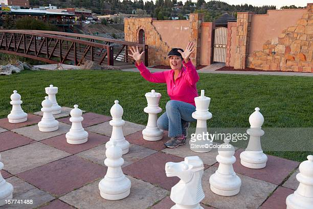 Woman playing chess with 1/2 life size pieces