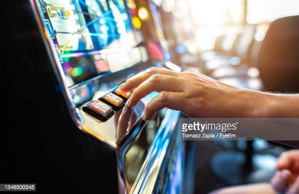 woman playing classic slot machine inside las vegas casino. one handed bandit game play. - bid stock pictures, royalty-free photos & images