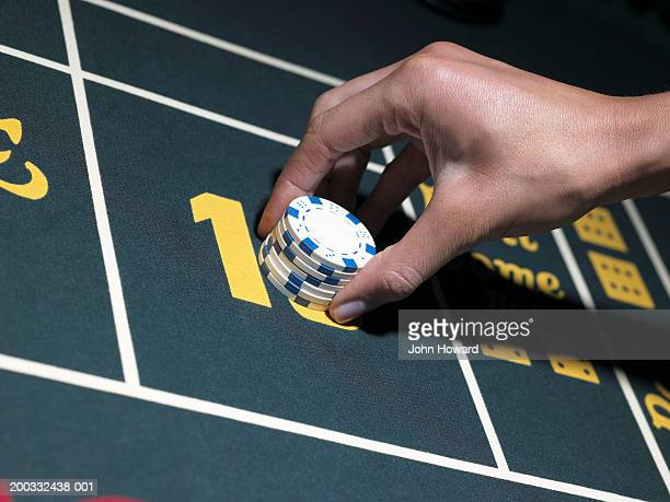 Woman playing craps, plaing chips on gaming table, close-up