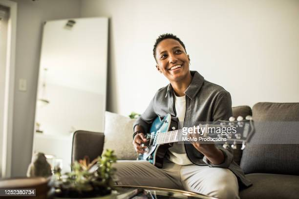 woman playing electric guitar in living room - authenticity stock pictures, royalty-free photos & images