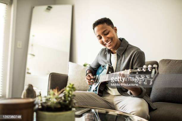 woman playing electric guitar in living room - lgbtq  and female domestic life fotografías e imágenes de stock