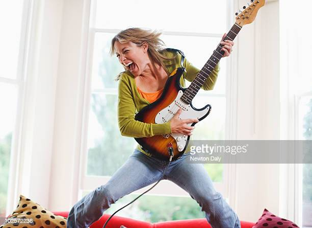 woman playing electric guitar in sitting room - electric guitar stock pictures, royalty-free photos & images
