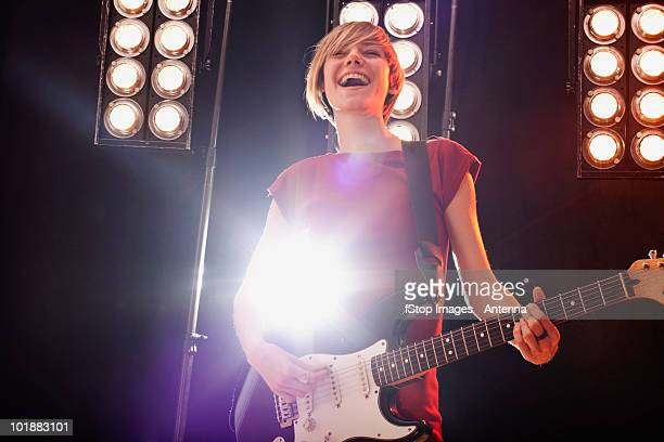 A woman playing electric guitar performing on stage