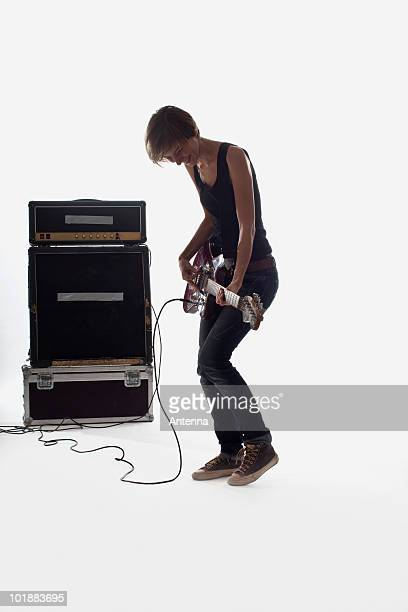 A woman playing electric guitar, studio shot, white background, back lit
