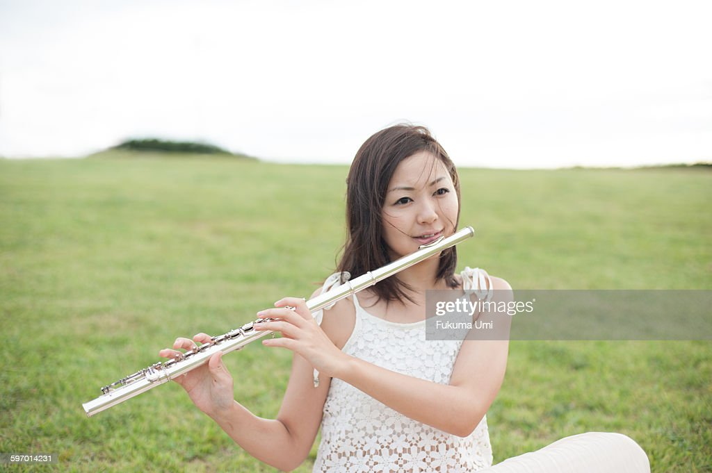 woman playing Flutist in field : ストックフォト