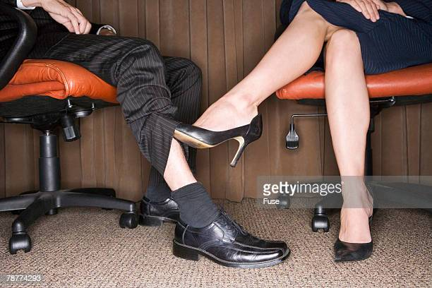 Woman Playing Footsie with Businessman