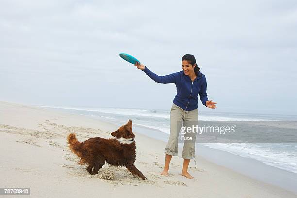 Woman Playing Frisbee with Dog