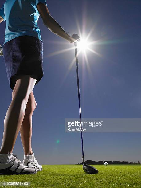 Woman playing golf, low section