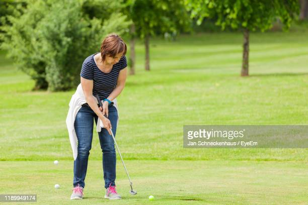 woman playing golf - jeans stock pictures, royalty-free photos & images