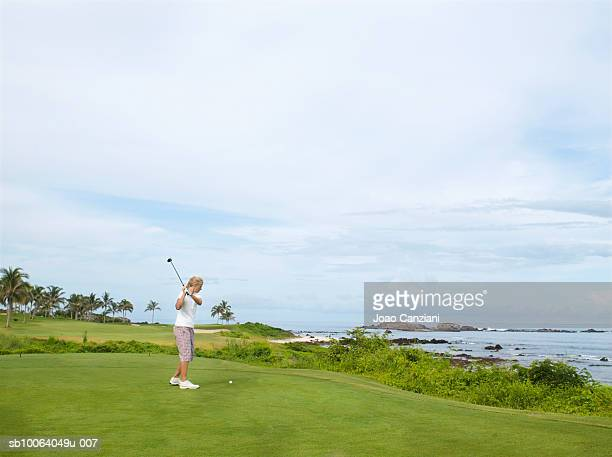 Woman playing golf, side view