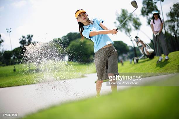 woman playing golf with woman in background - ゴルフ選手 ストックフォトと画像