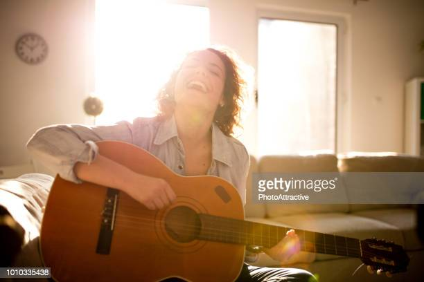 woman playing guitar and enjoying - plucking an instrument stock pictures, royalty-free photos & images