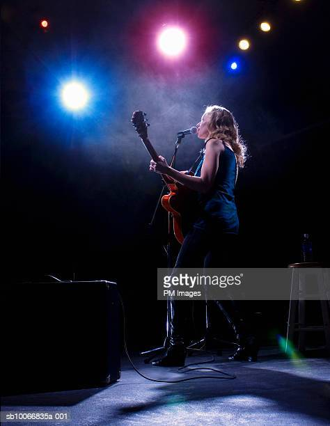 Woman playing guitar and singing on stage