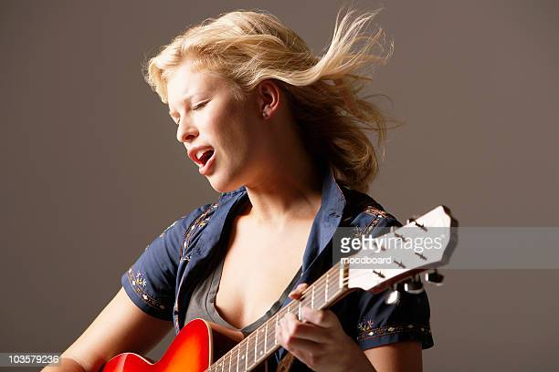 Woman Playing Guitar and Singing with windblown hair, close-up