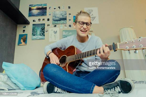 woman playing guitar in her bedroom - guitariste photos et images de collection