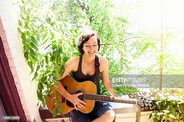Woman playing guitar on balcony