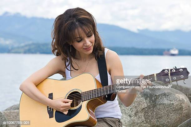 Woman playing guitar on beach