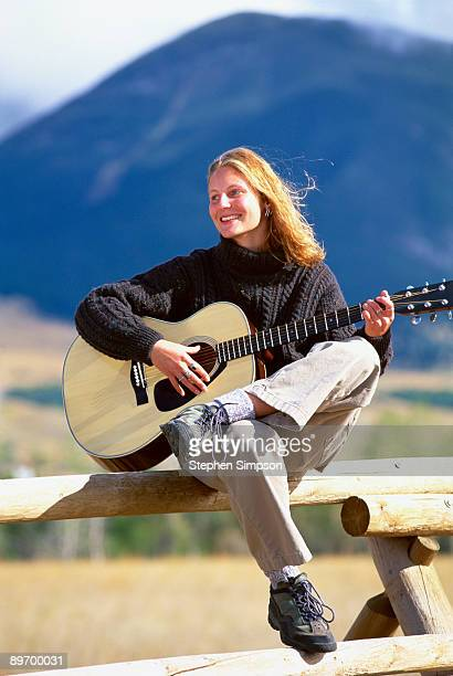 woman playing guitar on rustic fence - acoustic music stock pictures, royalty-free photos & images