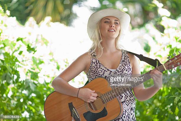 Woman playing guitar outdoors