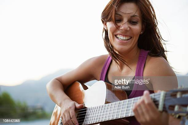 woman playing guitar - plucking an instrument stock pictures, royalty-free photos & images