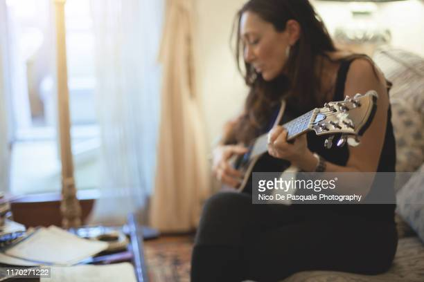 woman playing guitar - musician stock pictures, royalty-free photos & images