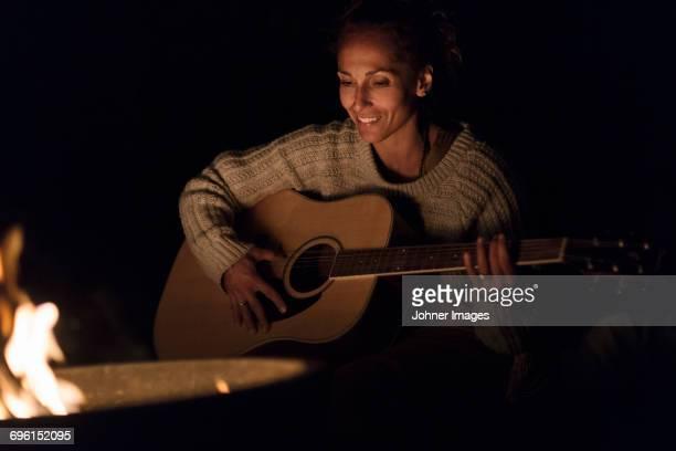woman playing guitar - pizzicare le corde di uno strumento foto e immagini stock
