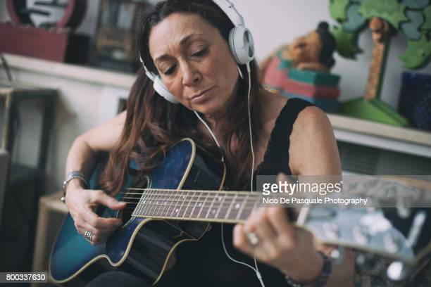 woman playing guitar - hobbies stock pictures, royalty-free photos & images