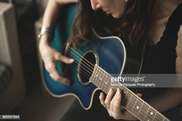 woman playing guitar - acoustic guitar stock pictures, royalty-free photos & images