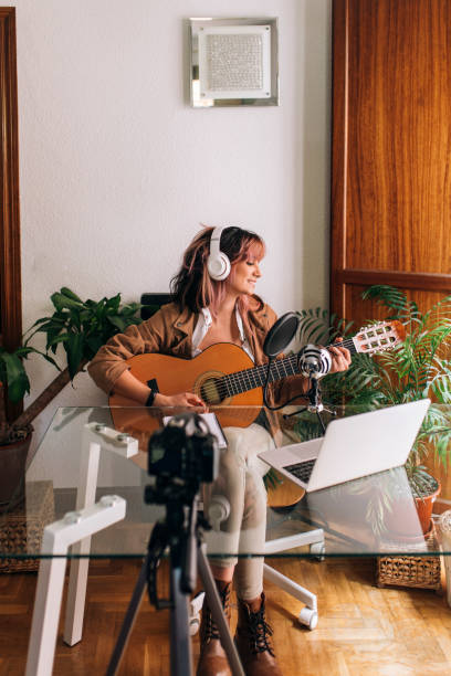 Woman playing guitar while filming at home