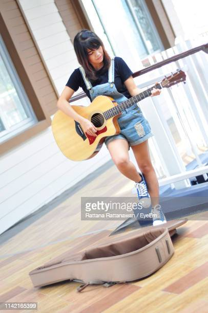 woman playing guitar while standing against railing - guitar case stock pictures, royalty-free photos & images