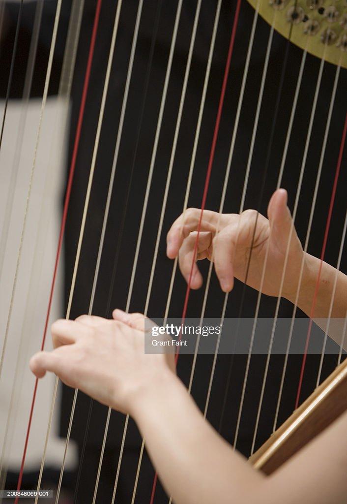Woman playing harp, close-up : Stock Photo