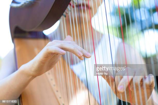 woman playing harp outdoors - string instrument stock photos and pictures