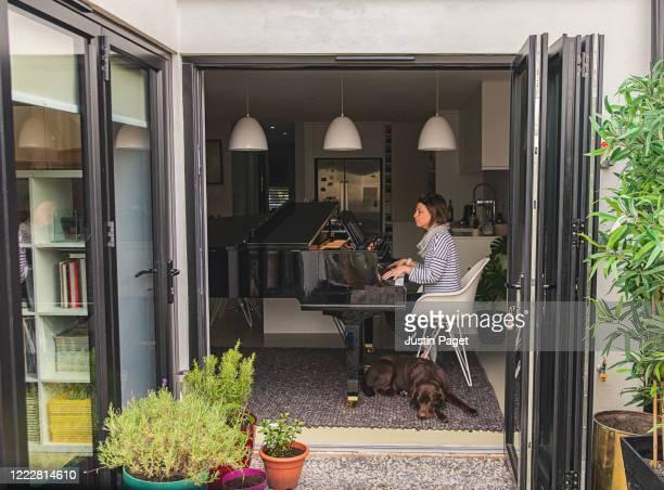 woman playing her grand piano at home - lockdown - fotografias e filmes do acervo