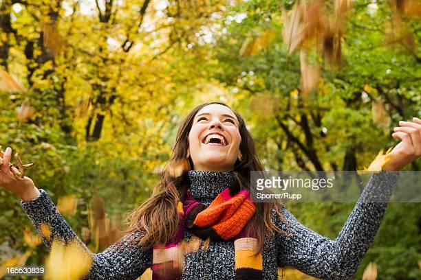 woman playing in autumn leaves - 投げる ストックフォトと画像