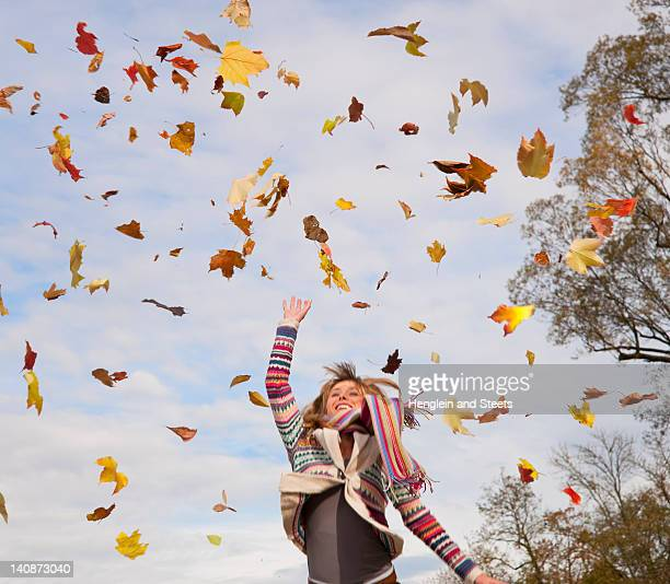 Woman playing in fall leaves