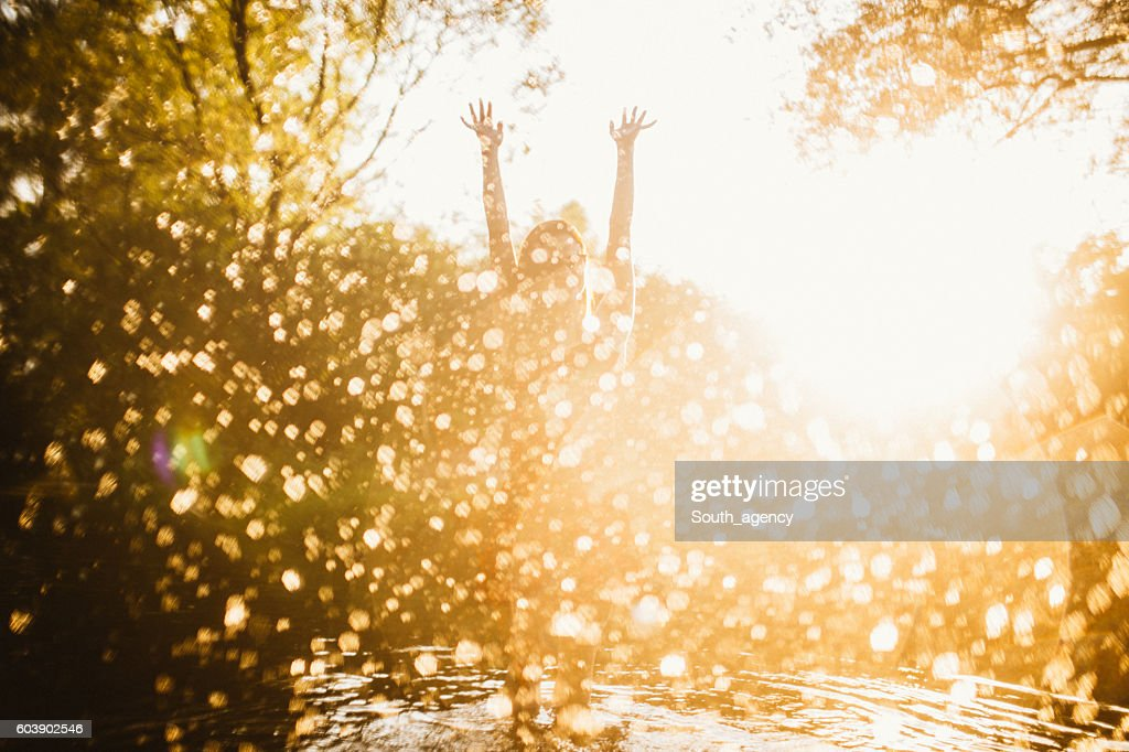 Woman playing in the river : Stock Photo