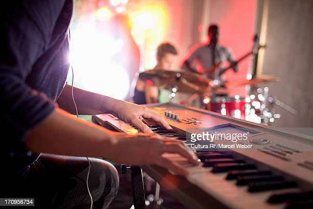 Woman playing keyboard, band in background