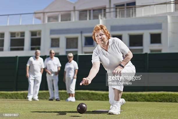 Woman playing lawn bowling on grass