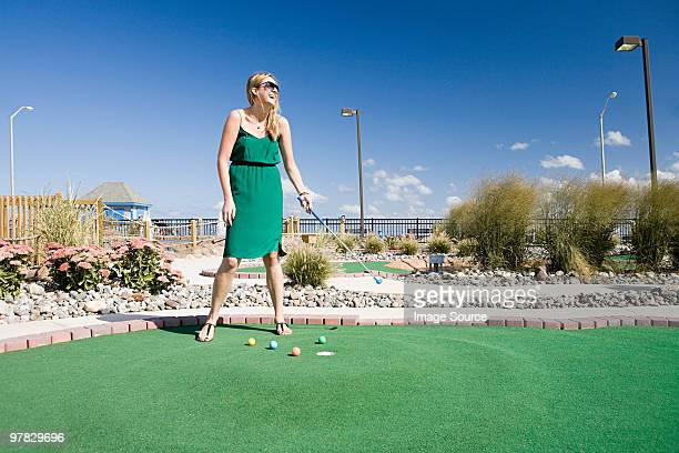 woman playing miniature golf - miniature golf stock photos and pictures