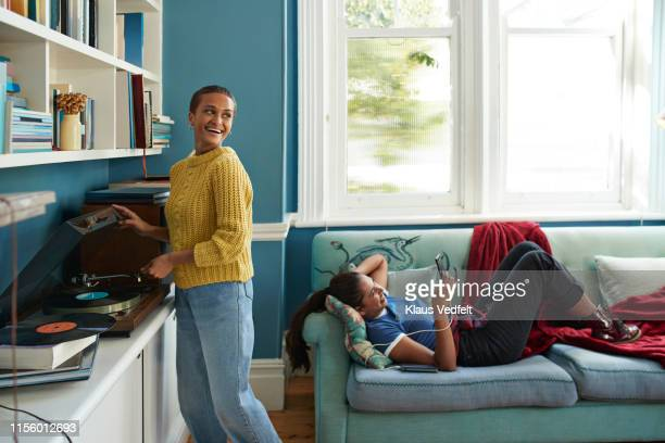 woman playing music and friend using phone - roommate stock pictures, royalty-free photos & images