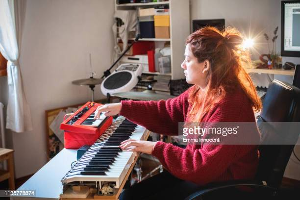 woman playing music on two keyboards - キーボード奏者 ストックフォトと画像