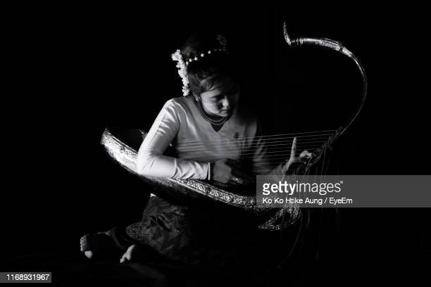 woman playing musical equipment against black background - ko ko htike aung stock pictures, royalty-free photos & images