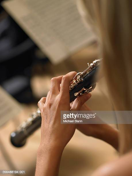woman playing oboe in orchestra, close-up, rear view - oboe stock-fotos und bilder