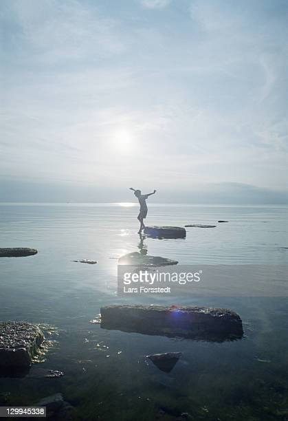 woman playing on rocks in lake - gotland bildbanksfoton och bilder