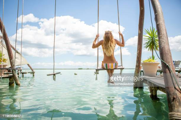 woman playing on swing over the sea, mexico - cancun stock pictures, royalty-free photos & images