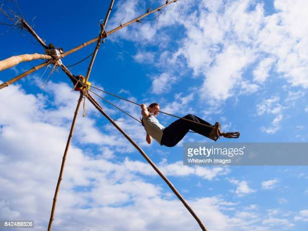woman playing on traditional tall bamboo swing in nepal - dashain stock photos and pictures