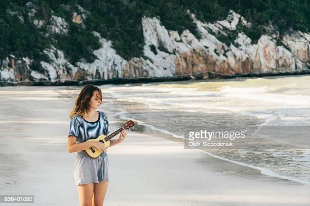 Woman playing on ukulele on the beach